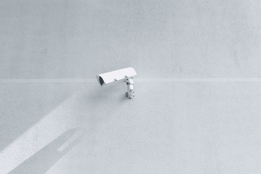 A security camera on a white wall