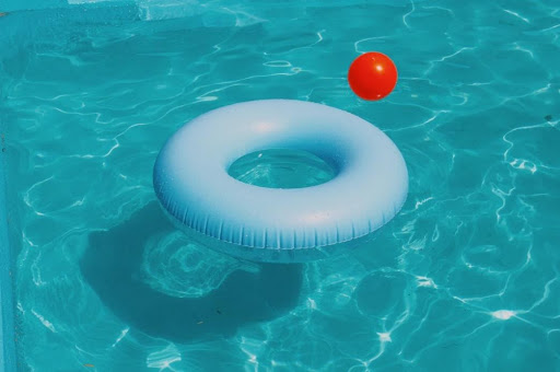 A tube and a ball in a swimming pool
